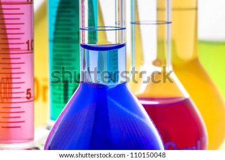 Laboratory glassware with liquids of different colors isolated over white background - stock photo
