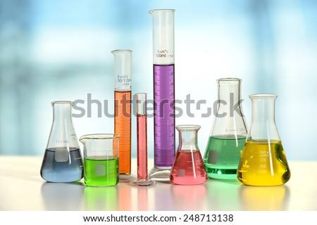 Laboratory glassware with liquids of different colors on white table - With clipping path on glass - stock photo