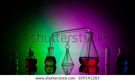 Laboratory glassware with liquids on dark colorful background