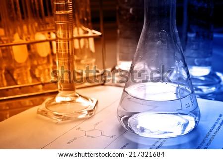 Laboratory glassware with science document   - stock photo