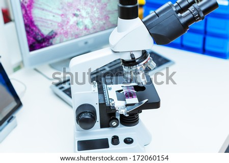 laboratory microscope with the image cells on the monitor - stock photo