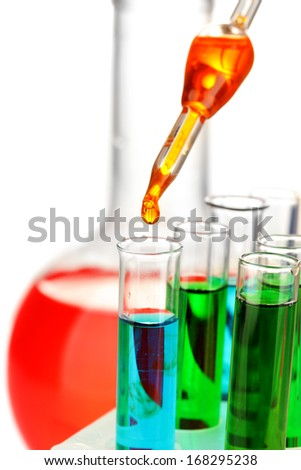 Laboratory pipette with drop of color liquid over glass test tubes, close up, isolated on white - stock photo