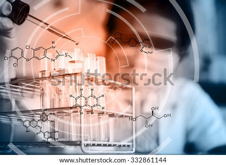 Laboratory pipette with drop of yellow liquid over glass test tubes for an experiment in a science research lab .Scientists In the laboratory with chemical equation - stock photo