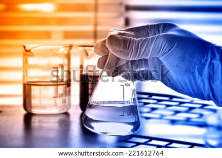 Laboratory research, flask in scientist hand with laboratory glassware  - stock photo