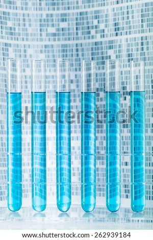 Laboratory sample test tubes with DNA gel in background - stock photo