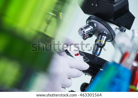 Laboratory scientist holding a slide containing a blood sample with microscope in the background