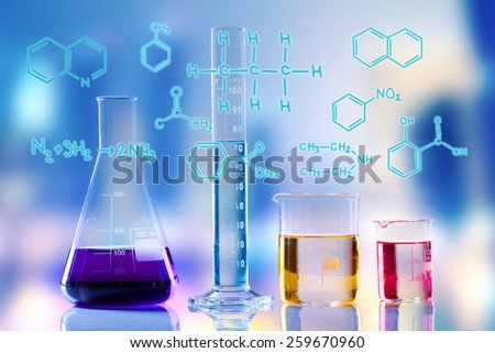 Laboratory tubes with colored liquids inside and formula on foreground - stock photo