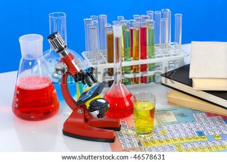 Laboratory ware, microscope and books - stock photo
