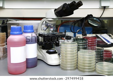 Laboratory workbench with a microscope, plates and reagents for microscopic analysis / lab bench for microscopic analysis - stock photo