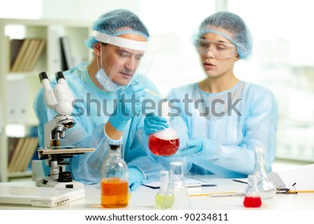Laboratory worker is about to inject fluid into smoky chemical substance during experiment