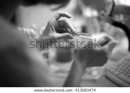 Laboratory worker taking material from a glass tube - stock photo