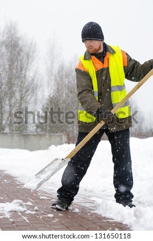 Laborer man road worker in uniform and reflective vest shoveling snow - stock photo