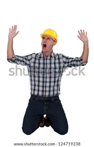 Laborer sitting on his knees screaming - stock photo
