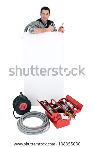 Laborer standing behind white sign for message - stock photo