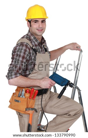 Laborer with drill on a ladder - stock photo