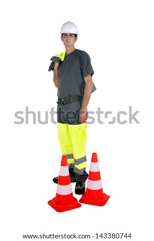 Laborer with traffic cones - stock photo