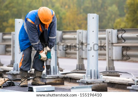 Laborer worker tightening bolts with Electric Impact Wrench tool during construction Road Works on installation traffic barrier - stock photo
