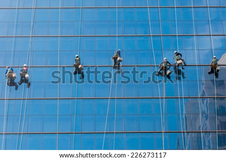 Laborers clean windows as a team on a skyscraper in downtown Seoul, South Korea
