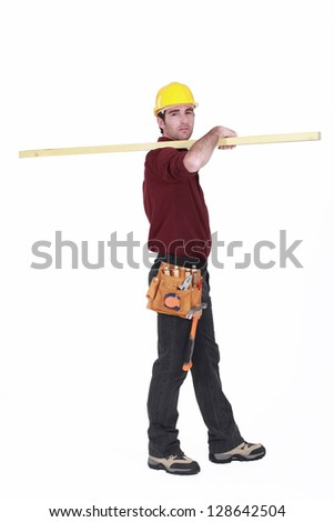 Labourer carrying a wooden plank - stock photo