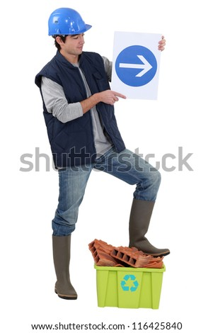 Labourer holding a traffic sign - stock photo