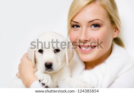Labrador puppy sitting on the hands of woman