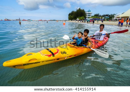 Labuan,Malaysia-April 30,2016:Happy family kayaking in the Labuan tropical beach at Labuan International Sea Sports Complex at Labuan,Malaysia on 30th April 2016.