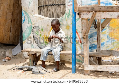 LAC ROSE reg., SENEGAL - APR 27, 2017: Unidentified Senegalese little boy sits on the wooden bench and plays with a wire. Still many people in Senegal live in poverty