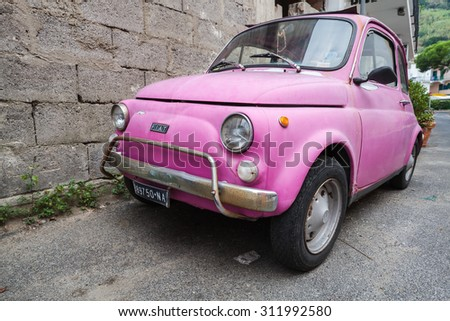 Lacco Ameno, Italy - August 15, 2015: Old pink Fiat Nuova 500 city car produced by the Italian manufacturer Fiat between 1957 and 1975 stands parked in a town, closeup photo