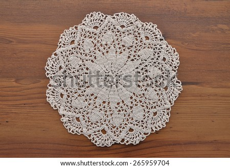 Lace doily on dark wood - stock photo