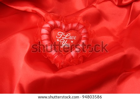 lace heart pillow on red silk - stock photo