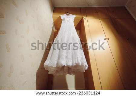lace white dress hanging at bride's room