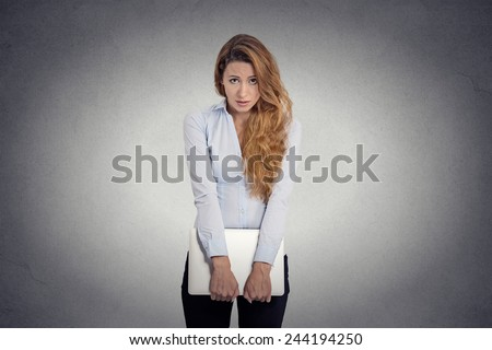 Lack of confidence. Insecure worried young woman holding laptop feels awkward isolated grey wall background. Human face expression emotion body language life perception   - stock photo