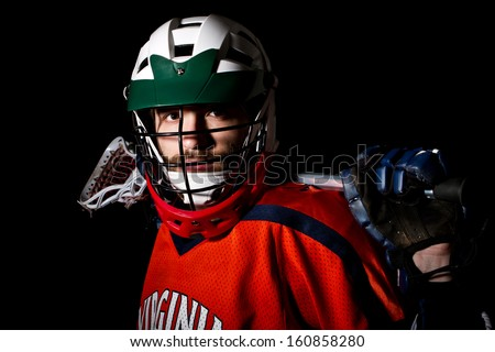 Lacrosse player wearing helmet and holding stick. Studio shoot on the black background. - stock photo