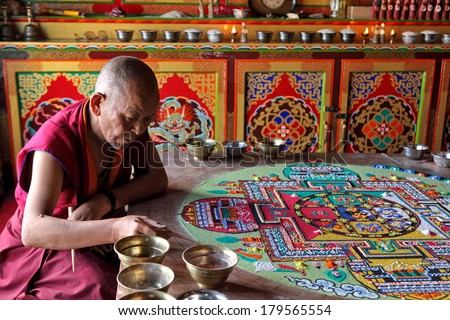 LADAKH, INDIA - SEPTEMBER 03, 2011: Buddhist monks making sand mandala in Diskit gompa at Nubra valley. Mandala - is a spiritual and ritual symbol in Hinduism and Buddhism, representing the Universe. - stock photo