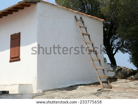 Ladder against a wall. An unsecured ladder leaning against a wall of a small whitewashed house in Greece. Shows health and safety issues and country ways as well as house maintenance. - stock photo