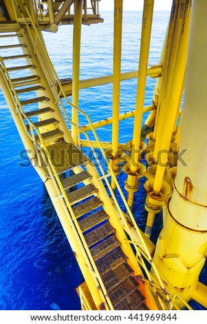 Ladder and aligned Oil and Gas Pipeline and Production slots in Petroleum offshore wellhead remote platform, Energy and petroleum industry, Oil and gas or Petroleum industry is major of the world. - stock photo