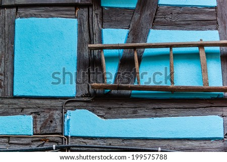 Ladder hanging on the wall of a turquoise half timbered building in France.