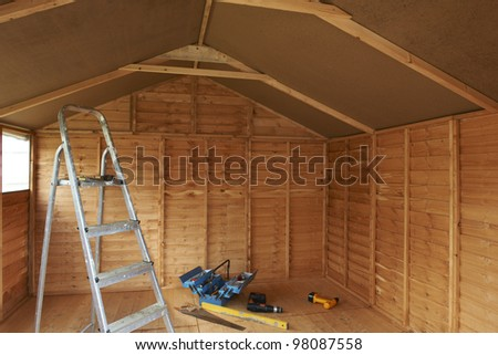 ladder in newly constructed shed with tools on the floor - stock photo