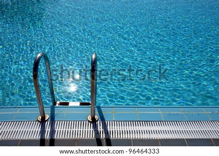 ladder leading into the refreshing crystal water of a pool