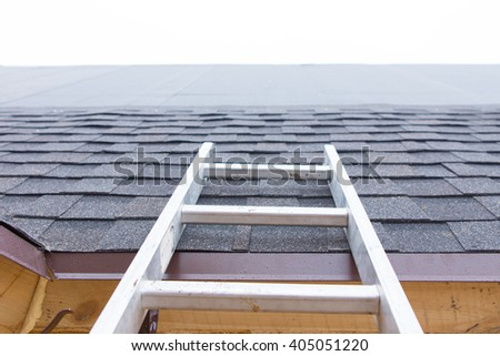 Ladder leading to an unfinished roof on a new house showing the installation of new roofing tiles and the waterproof membrane - stock photo