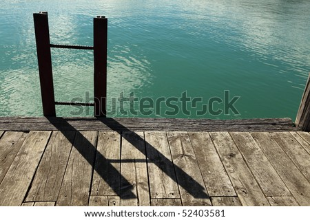 Ladder made from railway iron on a wharf with green sea behind.  Backlit on a sunny day. - stock photo