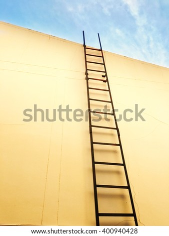 Ladder of success leading over the wall to the clouds. - stock photo