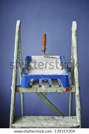 ladder, paint can and paint roller on blue background - stock photo
