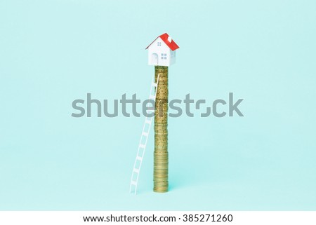 Ladder to climb a coin stack with your dreams house on top of it. - stock photo
