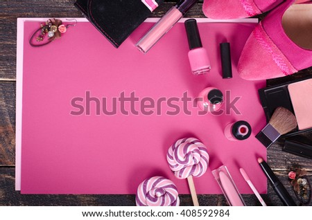 Ladies background - shoes, lipstick, nail polish, earrings, blush, lollipops on craft paper and wooden background.  Top view - stock photo