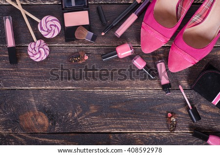 Ladies background - shoes, lipstick, nail polish, earrings, blush, lollipops on pink wooden wooden background.  Top view - stock photo