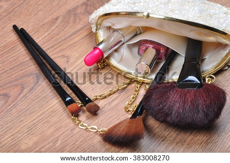 Ladies Bag for cosmetics with brushes, pink lipstick, nail polish on the brown wooden table. The concept of beauty and personal care - stock photo