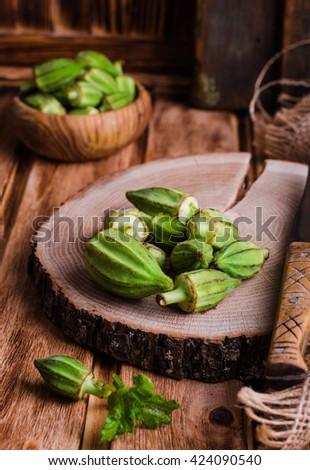 Ladies' finger or okra on round wooden chopping with some slices and knife.  Preparation of these healthy fresh edible green seed pods for cooking.  Selective focus - stock photo