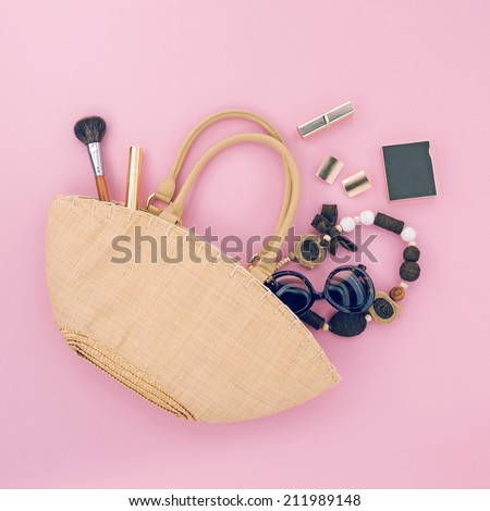 Ladies handmade bag with different accessories on pink background - stock photo