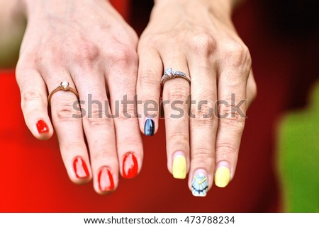 Ladies hold their hands with engagemet rings behind each other